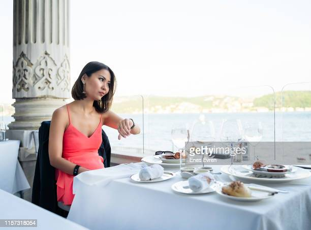 exhausted woman waiting her date, checking the time in restaurant - thinking of you card stock pictures, royalty-free photos & images