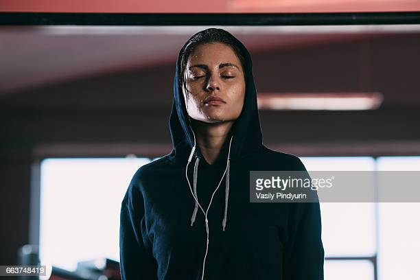 exhausted woman wearing hooded shirt standing with eyes closed at gym - hoodie headphones stock pictures, royalty-free photos & images