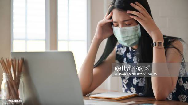 exhausted woman wearing mask using laptop at home - stress coronavirus stock pictures, royalty-free photos & images