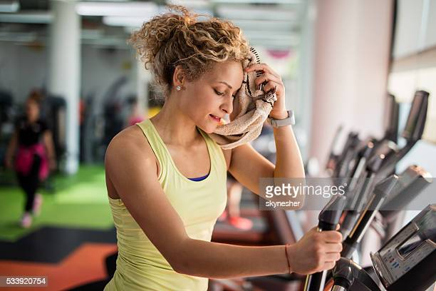 Exhausted woman wiping sweat with a towel in a gym.