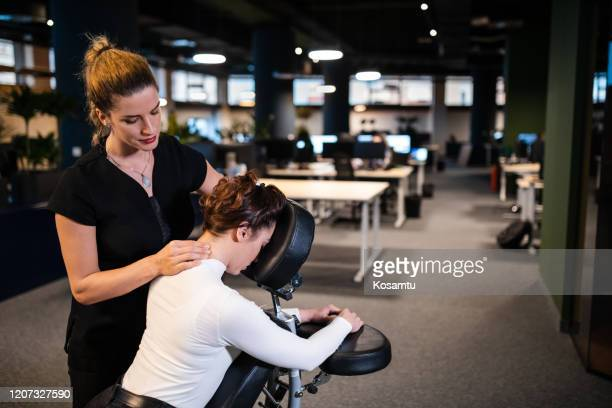 exhausted young business woman enjoying neck massage after long hard working office day - massaging stock pictures, royalty-free photos & images