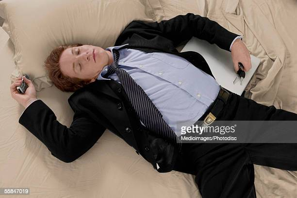 Exhausted young businessman lying on bed with keys, laptop and mobile phone