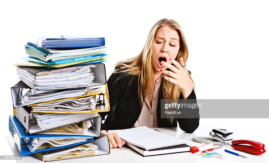 Exhausted Young Businesswoman Yawning At Her Overloaded Desk