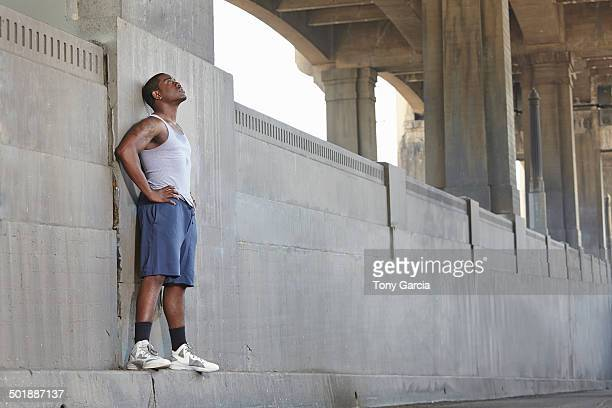 Exhausted young male runner leaning against city bridge