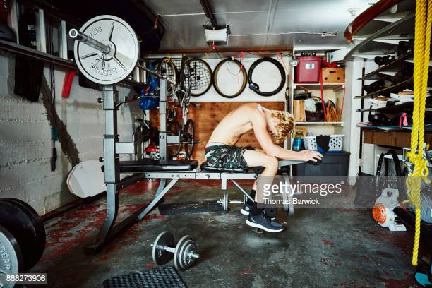 Exhausted young man resting after working out in basement gym