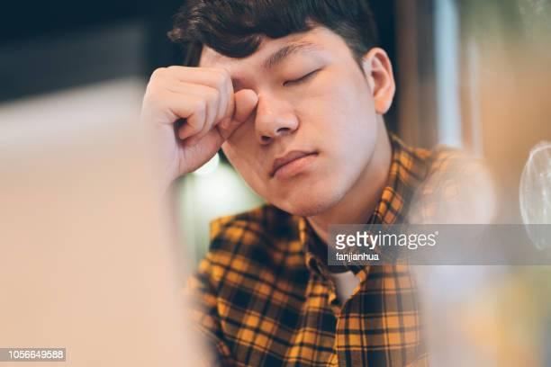 exhausted young man rubbing eyes in cafe - frustração imagens e fotografias de stock