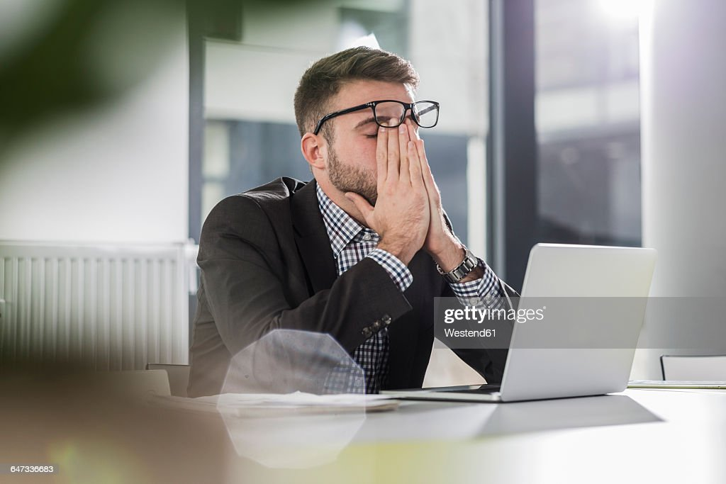 Exhausted young man with laptop in office : ストックフォト