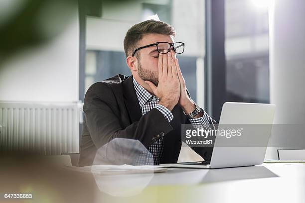 exhausted young man with laptop in office - arbeiten stock-fotos und bilder
