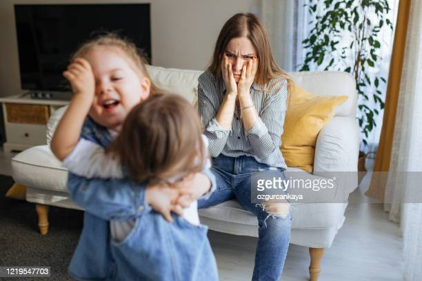 exhausted young mother annoyed from loud children - anti quarantine stock pictures, royalty-free photos & images