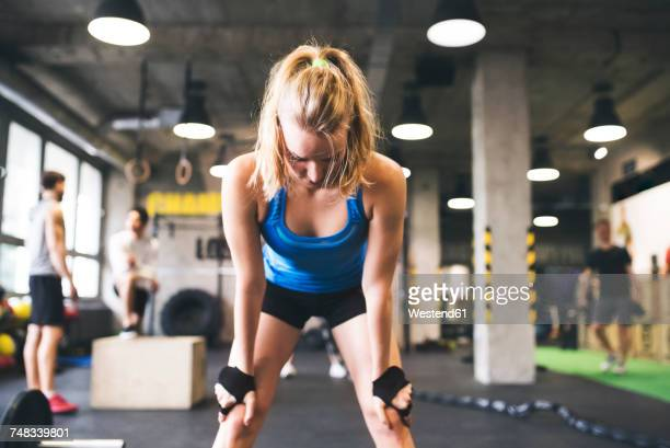 Exhausted young woman in gym having a break