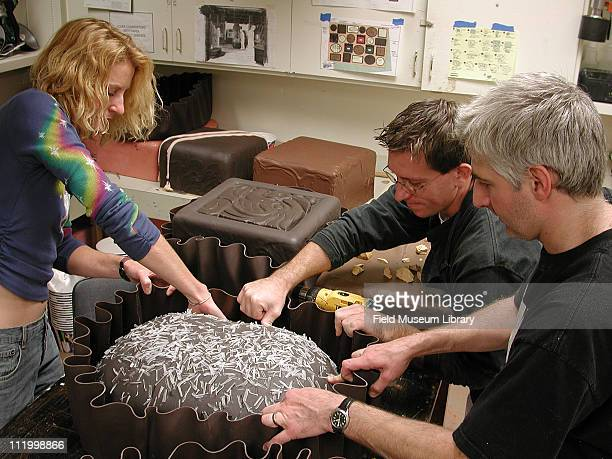 Exhibit preparators in the process of making enlarged models of a box of chocolates for Chocolate exhibit in the replication shop at the Field Museum...