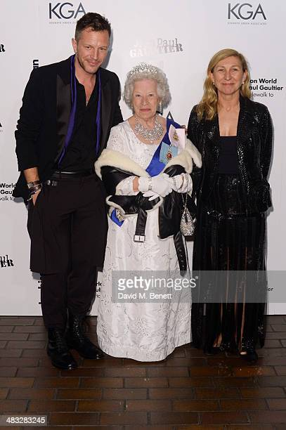 Exhibition curator ThierryMaxime Loriot a Queen Elizabeth II impersonator and Odile Gilbert attend an exclusive reception for 'The Fashion World of...
