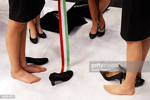 Exhibition hostesses stand without shoes ahead of the visit of German Chancellor Angela Merkel for an opening tour of the Hannover Messe trade fair...