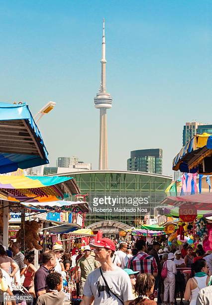 Exhibition Place Event A large crowd enjoys an outdoor event in the city of Toronto In the background the famous CN Tower is seen towering over the...