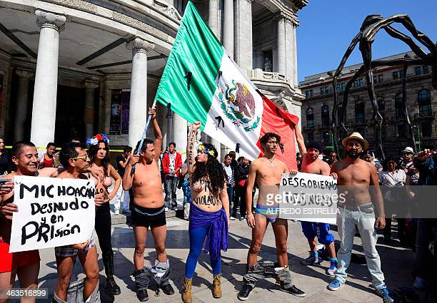Exhibitionist feminist protest group FEMEN activists hold a sign reading 'Naked Michoacan' as they demonstrate against Michoacan State's government...