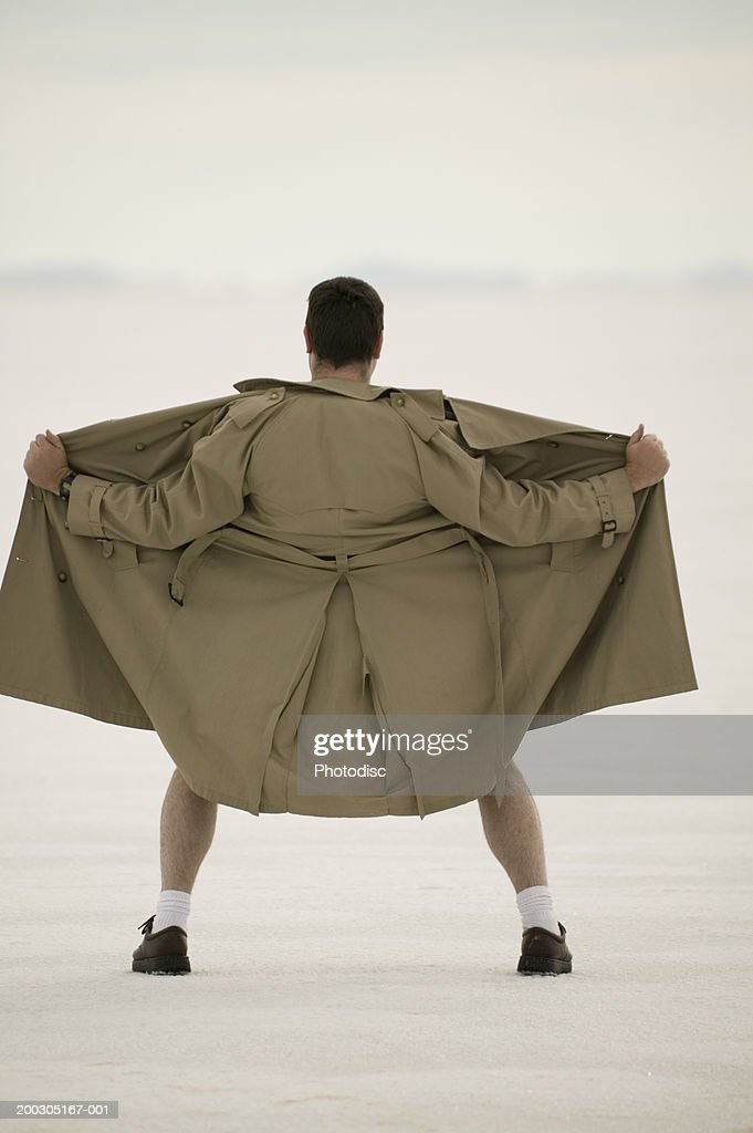 Exhibitionist spreading front of coat, at beach : Stock Photo