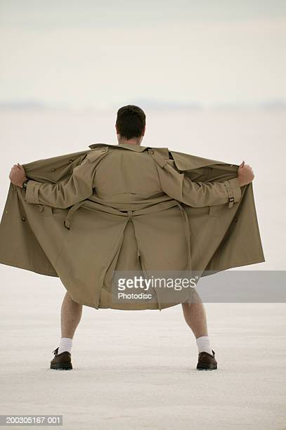 exhibitionist spreading front of coat, at beach - male flashers stock photos and pictures