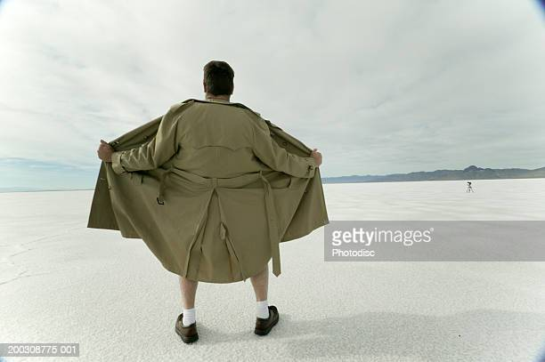 exhibitionist spreading open coat in desert - male flashers stock photos and pictures