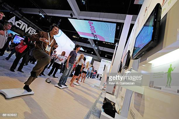 Exhibitor Carrie Fistel takes direction from Melissa Fajr as she plays Wii Fit Plus at the Nintendo booth during the Electronic and Entertainment...