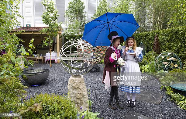 Exhibitors dressed as 'The Hatter' and 'Alice in Wonderland' drink tea whilst sheltering from the rain under an umbrella on the David Harbor stand at...