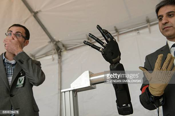Exhibitors from Johns Hopkins Applied Physics Laboratory stand with a robotic hand during the Defense Advanced Research Projects Agency Demo Day at...