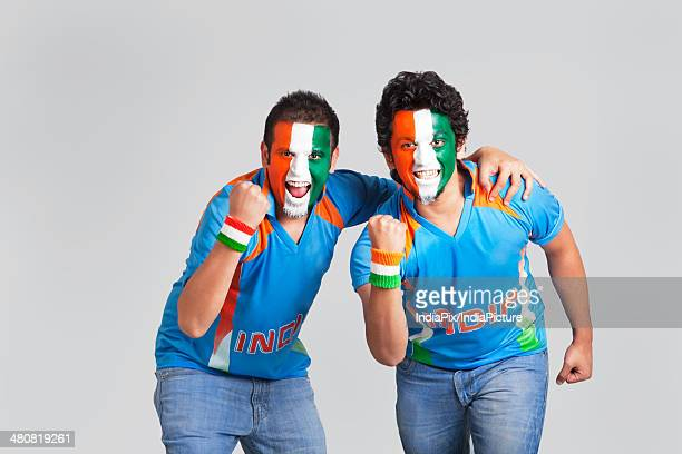 Exhilarated male cricket supporters with a painted face in tricolor cheering over gray background
