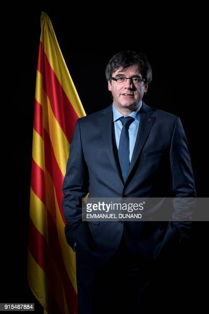 Exiled former Catalan leader Carles Puigdemont poses in front of a Catalan flag during a photo session in Brussels on February 7 2018 / AFP PHOTO /...
