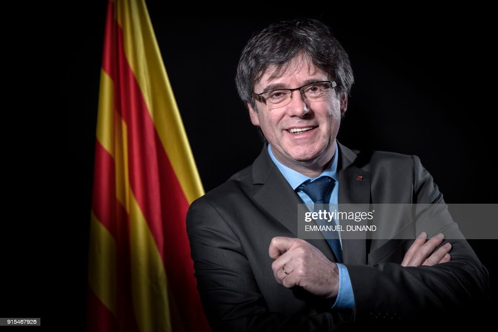 TOPSHOT - Exiled former Catalan leader Carles Puigdemont poses in front of a Catalan flag during a photo session in Brussels on February 7, 2018. / AFP PHOTO / Emmanuel DUNAND