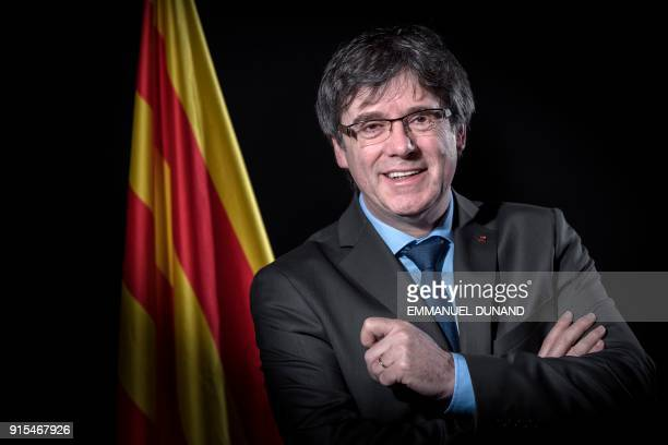 TOPSHOT Exiled former Catalan leader Carles Puigdemont poses in front of a Catalan flag during a photo session in Brussels on February 7 2018 / AFP...