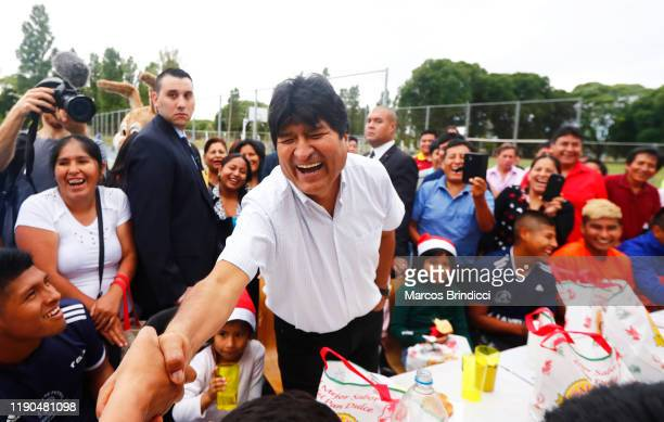 Exiled former President of Bolivia Evo Morales laughs as he shakes hands during a Christmas breakfast with members of the Bolivian community of...