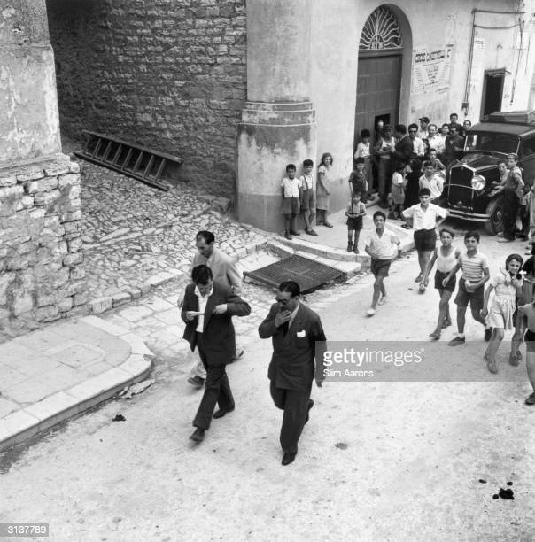 Exiled Mafia boss Charles 'Lucky' Luciano and entourage draw a crowd mainly of children as they walk down a street in Sicily