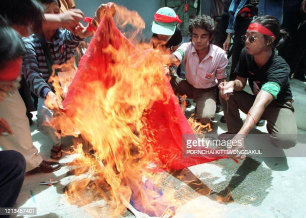 Exiled Myanmar protesters burn a Myanmar national flag during a protest in front of the Myanmar embassy in Bangkok 27 May, 1999 to mark the ninth...
