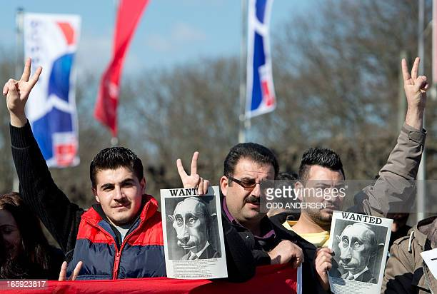 Exiled Syrians gesture as they hold leaflets with a picture of Vladimir Putin that reads 'Wanted ' to stage a protest against the Russian President...