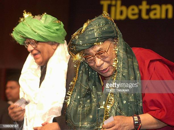 Exiled Tibetan spiritual leader the Dalai Lama and former Indian president R Venkataraman wear Muslim headdresses presented to them by a Muslim...