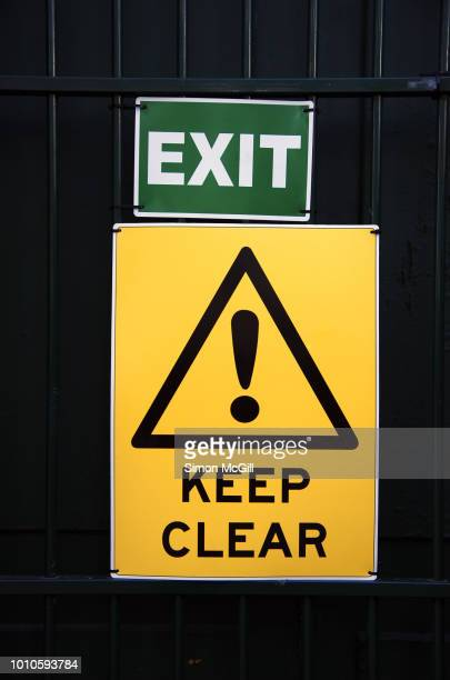 Exit and Keep Clear signs attached to the security door to a construction site
