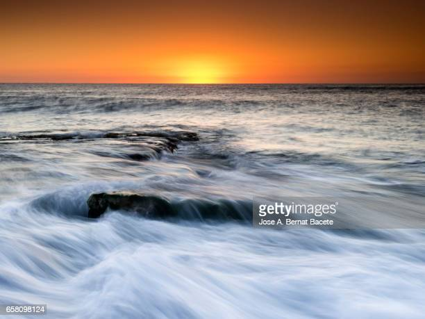 Exit of the Sun of orange color, on the surface of the sea, in a zone of coast with rocks and waves in movement