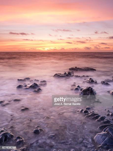 exit of the sun with a sky of clouds of orange color, on the surface of the sea, in a zone of coast with rocks and waves in movement. tabarca island,  mediterranean sea, spain - rock formation stock pictures, royalty-free photos & images
