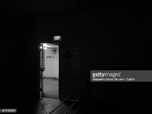 Exit Sign Above Open Door In Darkroom
