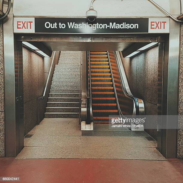 exit sign leading towards steps and escalator in underground subway station - escalator stock pictures, royalty-free photos & images