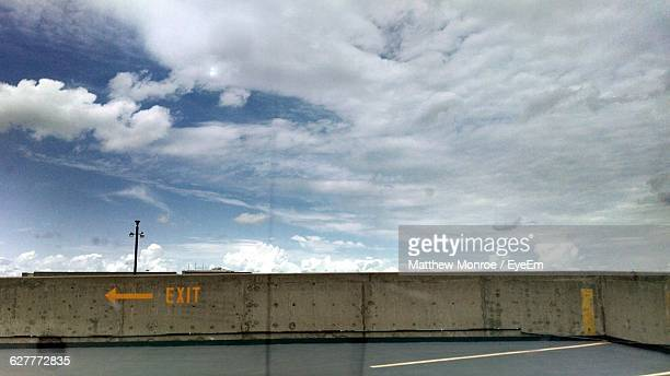 Exit Sign On Surrounding Wall Against Sky