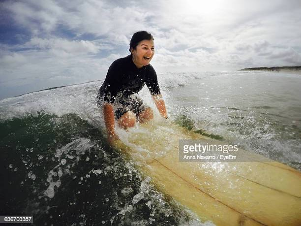 Exited Woman Surfing On Sea Against Cloudy Sky