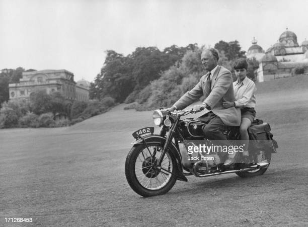 ExKing Leopold III of Belgium takes his son Prince Alexander of Belgium for a ride on the back of a motorcycle around the grounds of the Royal Palace...