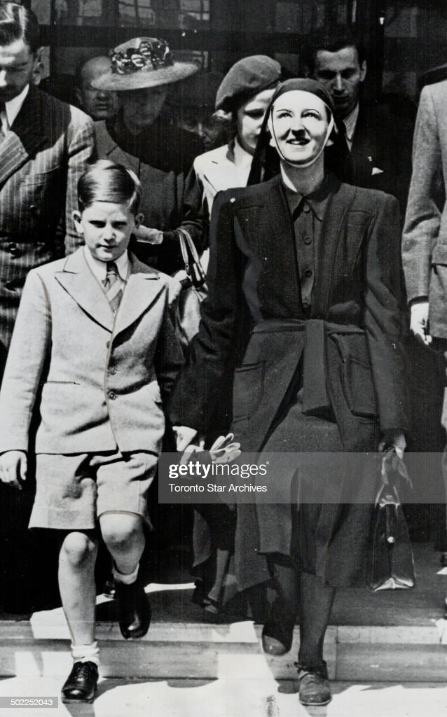 Ex-king Simeon, nine, of Bulgaria, grandson of the dethroned Victor Emmanuel of Italy, holds hand of Queen Mother Giovanna at Istanbul, Turkey, en route to Egypt