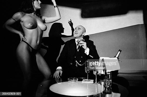 ExLondon gangster Dave Courtney enjoys his champagne and cigar lifestyle while watching a dancer at a London table and pole dancing nightclub May 2001