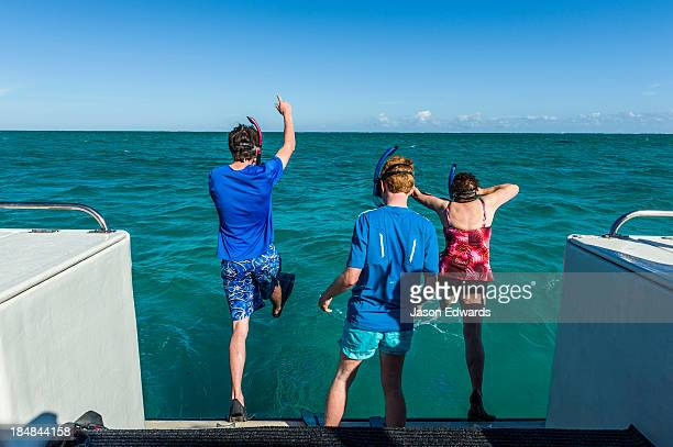 Tourists leap of the rear of a boat to dive with Whale Sharks.