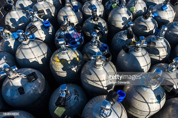 A collection of scuba diving oxygen tanks in a steel cage.