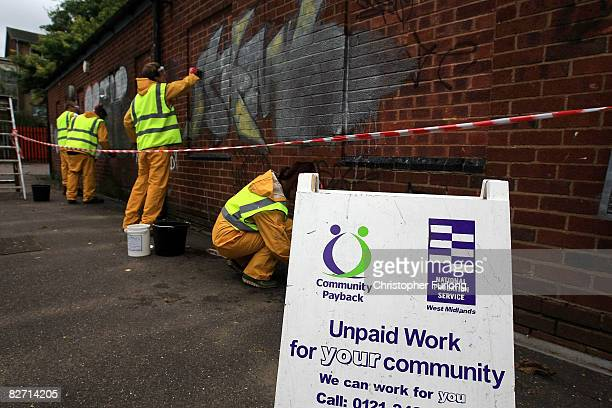 Ex-offenders clean off graffitti as part of their community service at The Malcolm Locker Youth Centre during a visit by Secretary of State for...