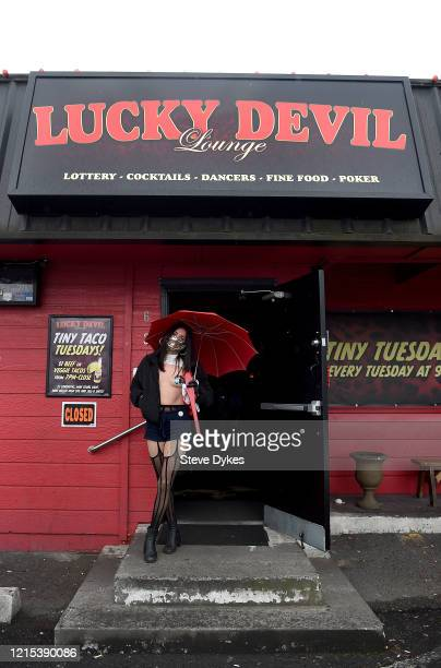Exotic dancer Lous stands in the doorway of the Lucky Devil as she waits to go out on a delivery on March 27 2020 in Portland Oregon The local...