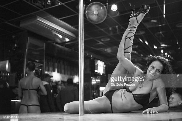 CONTENT] Exotic Dancer / Stripper / Pole Dancer smiles at audience while doing a dance move in busy strip club Black and white