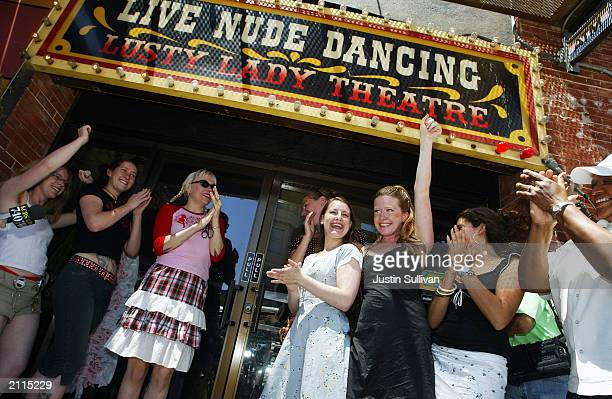 Exotic dancers cheer after cutting a large garter belt to officially reopening the Lusty Lady strip club June 26 2003 in San Francisco The dancers...
